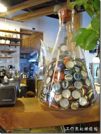 [台南]《a room,房間》。吧台上面放了一個特大型的錐形玻璃瓶,讓我想起了以前化學課,玻璃瓶內放滿了啤酒的酒瓶蓋,不知道意思是不是說把所有的啤酒混合起來的滋味?