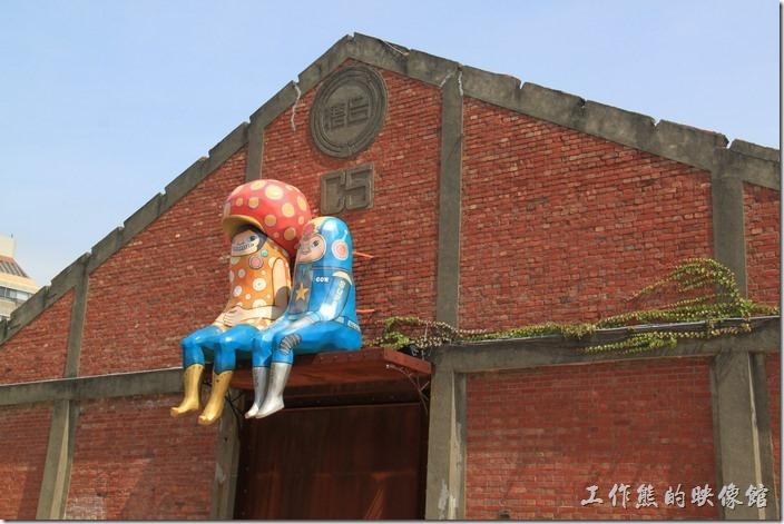高雄-駁二特區。真羨慕這兩個小朋友就這樣坐在台糖舊倉庫的大門上面!什麼也不用作,悠閒地坐在高處看過往遊客,不過也不是那麼好就是了,因為不能到處晃啊!還要成風吹與淋。這兩個小朋友,一個有著鮮艷點點帶了一頂類似草菇造型帽子,另一個應該是外太空牛仔吧!因為身上有著星星及「COW」字樣,還有像極火箭造型的大頭。