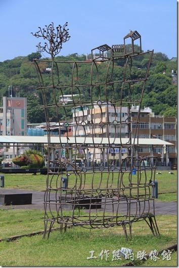 高雄-鐵道故事館。傘形鐵支路上的大型裝置藝術。山丘上的房子與樹木