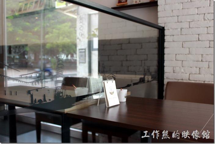 台南-綠帕克咖啡館。桌子與桌子間的隔牆則巧妙的利用厚玻璃並貼上許多黑色的景物剪影,讓桌與桌之間有點距離又沒有距離。