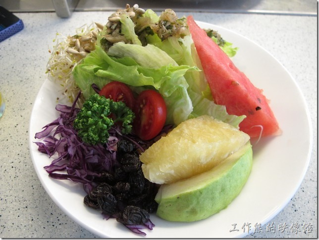 沙拉。有一顆小蕃茄、一塊鳳梨、一塊芭樂、一片西瓜、一大把的葡萄乾、去殼的葵瓜子、生菜、玉米、苜蓿芽…等。沙拉的份量真的很多,吃完後很有飽足感。