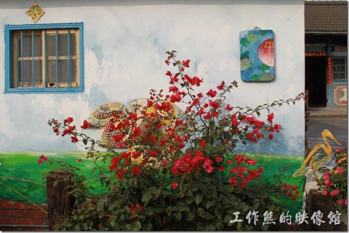 台南-土溝村(竹仔腳)。「幾米」裝置藝術的隔壁有住家,這間「白毛伯」的家牆壁上有彩繪,還掛了一塊畫著「平安」兩字的覘板。九重葛後面還有一隻蝸牛爬在樹葉上,象徵「安居樂業」。