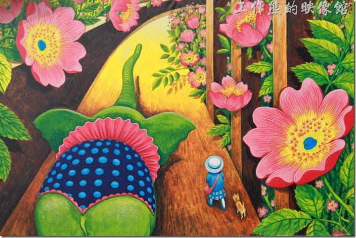 台南-土溝村(幾米)。在「幾米」塑像身後的牆壁上有一幅幾米色彩鮮艷的畫作,大象、小狗陪著小女孩走在充滿巨型花朵的道路上。