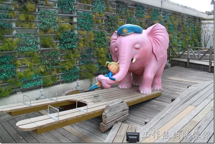 花蓮-翰品酒店。游泳池旁有一隻踩在蹺蹺板上面的大象正與小女孩擁抱在一起,他們正等著和遊客們比賽重量。