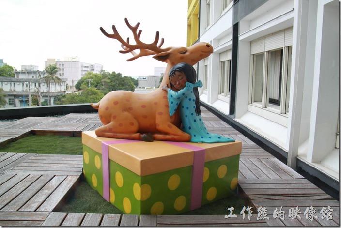 花蓮-翰品酒店。三樓的陽台上有個穿著睡衣的小女孩站在一個禮物盒子上,正抱著一隻靡鹿,似乎在感謝麋鹿送來禮物。