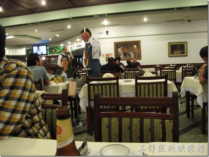 巴西窯烤OK-Grill。穿著白色上衣與灰色圍裙的服務生正拿著各式烤肉穿梭在各餐桌間位客人服務。