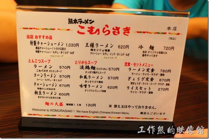 日本北九州,熊本拉麵こむらさき本店。桌上有菜單,特色叉燒拉麵1030円、王樣拉麵620円、拉麵570円、昆布拉麵570円、叉燒拉麵670円、納豆拉麵600円,換算成台幣價錢大概NT$150~NT$180左右,在日本這樣的價錢不算貴。