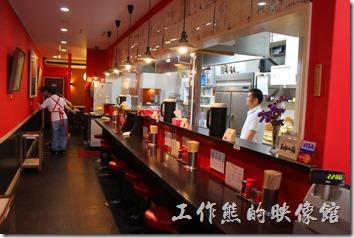 日本北九州,熊本拉麵こむらさき本店。「熊本拉麵こむらさき本店」店內吧台的環境,還有透明的廚房。