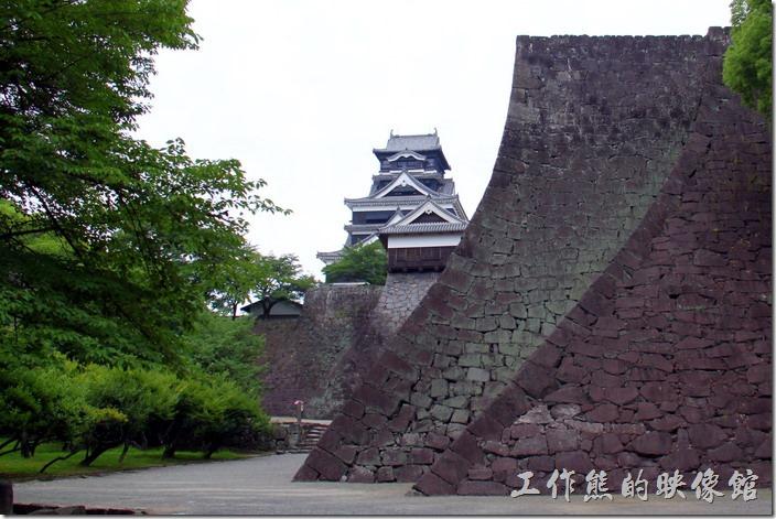 日本北九州-熊本城。好不容易可以看到熊本城的天守閣了,但還好一大段的距離。這張照片也正好可以表現出熊本城內「兩樣石牆」的建築風格。照片最右邊深色的石牆是熊本城年代最久遠的石牆,坡度較緩;隨著技術的革新與進步,左邊顏色較淺石牆可見其坡度明顯便陡了,可以看得出來是後來加蓋的。石牆的年代差別也可以在大小天守閣的石牆上發現。