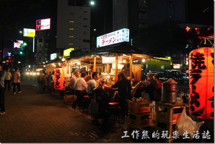 日本北九州-中洲屋台(路邊攤)。這裡的屋台生意好壞似乎是從最前面的攤子一路往下排,猜想可能是越前面的攤子,其資格越老,客人也就越多的緣故吧!當天來這裡的幾乎都是觀光客。