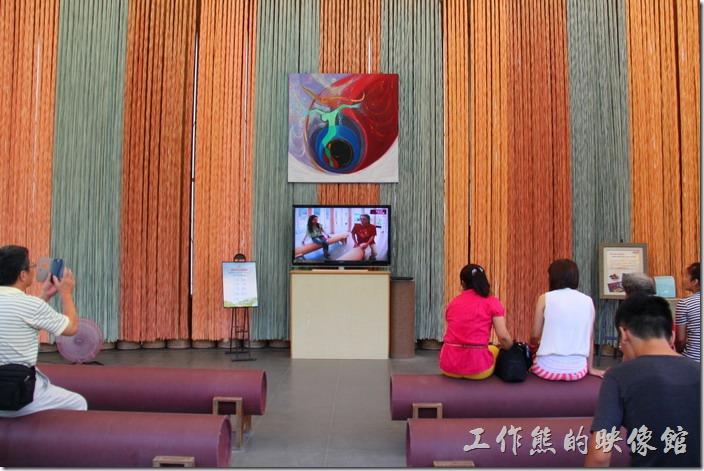 南投紙教堂內有許多「紙管」橫躺當作椅子,不過上面有包覆一層外衣,所以不明白的朋友可能不知道這就是紙做的椅子,現在中間擺了一台電視機,播放紙教堂的一些簡介影片。