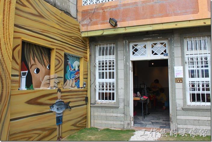 【安平●運河路7號】創意市集的大門,門的右手邊請人家畫了有趣的圖案,有個小孩站在窗後偷看。