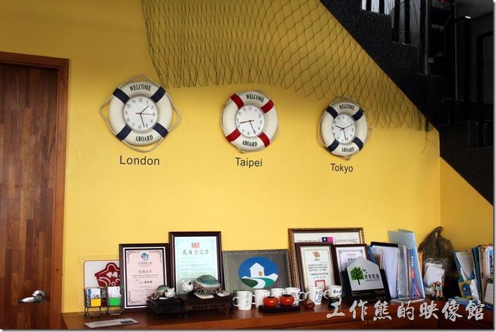 屏東-林邊東港-發現號祕境民宿。櫃檯前有倫敦、台北、東京時間的時鐘。
