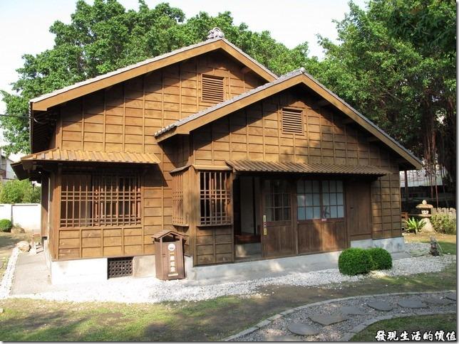 台鹽日式建築的外觀,有著前後雙屋脊,照片中隱約可以看見其背後的老榕樹生長得長茂盛。