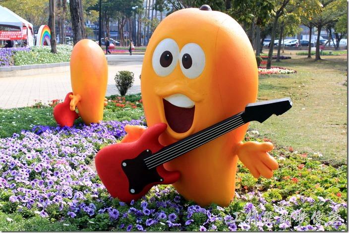 台南-2015百花祭。芒果動心弦。台南特產的芒果Q版公仔彈奏優美的音符,打動春遊水萍溫公園的遊客心弦。
