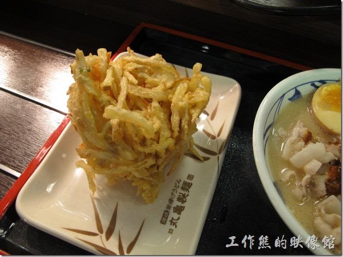 台南新光三越-丸龜製麵烏龍麵。取麵之後,老婆已經迫不及待的夾起一塊「牛蒡炸蔬菜」NT$35,她說這個很好吃,一定要點來吃。