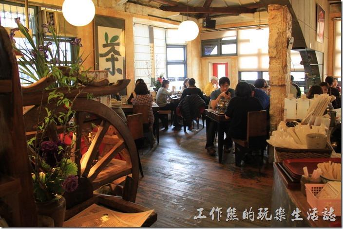 「台南-奉茶來恁兜」餐廳內的裝潢。中間用了一個清水模做了一個半圓形拱牆來強化老屋的結構。