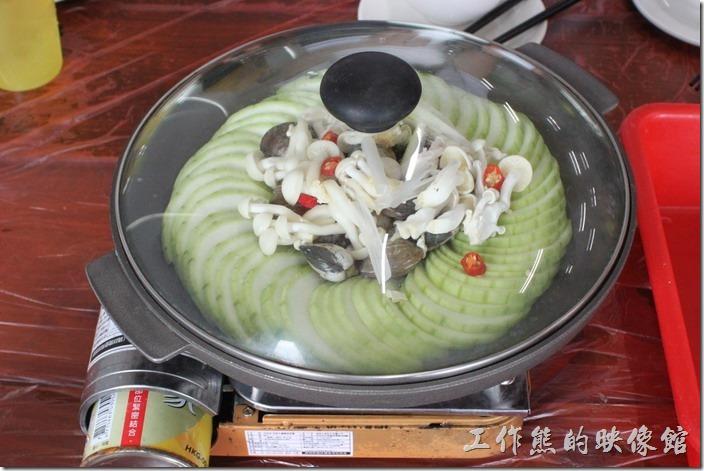 宜蘭-田媽媽瓜瓜風味餐。絲瓜蛤蠣,這道菜非常的特別,服務人員把切好的生絲瓜、蛤蠣、金針菇及辣椒與調味放在火鍋內,然後點火,絲瓜受熱後會慢慢的滲出湯汁來,滾燙的湯汁剛好可以煮熟其他的食材。