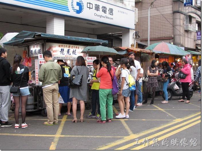 瑞芳火車站前華記與阿霞兩攤龍鳳腿小吃攤前排隊的民眾。