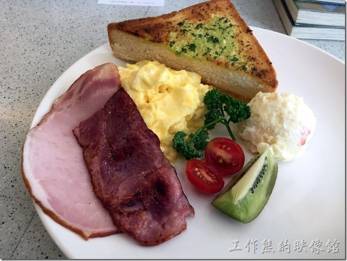 台南-Oilily早午餐。主菜上場了。擺盤的感覺怎麼全部偏一邊,這是故意的嗎!有一片培根、一片火腿(早期有兩片),一顆切半的聖女小蕃茄、一小片奇異果(過熟)、一團馬鈴薯泥(冰的)、炒蛋(份量好大)。工作熊這次點的是香蒜厚片。厚片還不錯吃,蒜味建議可以在塗多一點。這裡的火腿及培根是工作熊喜歡的口味,非常的鮮嫩任,可惜這次來份量變小了,而且剛煎好就直接放上盤子,一大層油在盤子內盪啊盪的讓人覺得不適很舒服,感覺有點小敗筆。