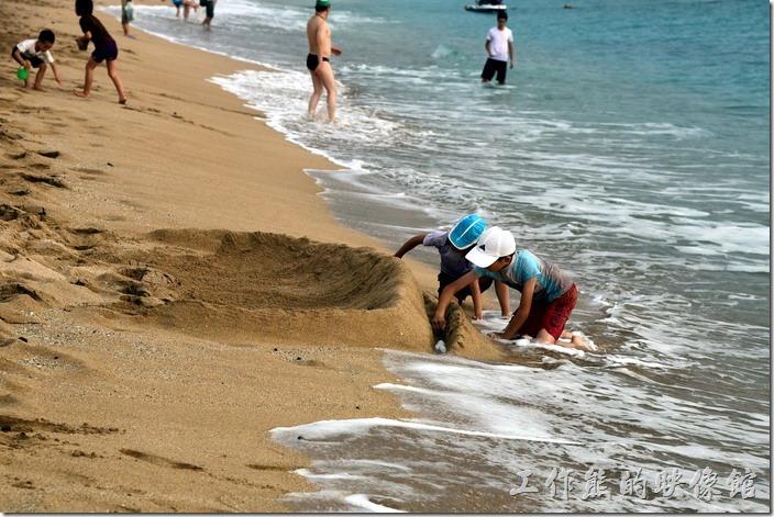 墾丁白沙灣。沙灘上玩沙雕的小朋友!
