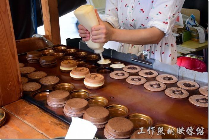 台南-宇田家菓子燒。店員正在賣力製作菓子燒,其製作的方式其實與車輪餅差不多,都必須要做出兩半然後合在一起,但材料不同而已。注意看美眉的手都是燙傷的痕跡。
