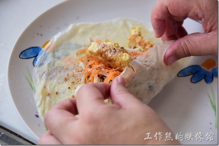 包潤餅的時候可以選擇先捲成圓筒然後左右折邊,或是先從下往上折,然後把左右內折,最後把上面下折,隨自己高興,別讓食材掉出來就好了。
