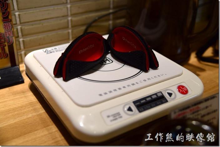 日本京都-麺屋もり拉麵。工作熊發現這家店的每個桌子上都有個電磁爐,而且這電池爐的上面還放了兩個很像水餃的布織物,一開始實在百思不得其解這到底使什麼,後來餐點上來後,才發現這個原來是方便客人可以用來拿取盛熱湯鐵鍋兩個耳朵用的,這樣客人才不會燙傷手!真貼心!