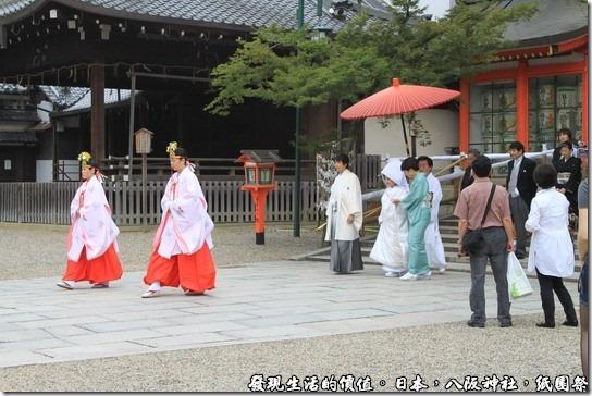 八坂神社-紙園祭,新人的前面有兩位前導,還有人為新娘特別撐傘,後面還跟著家屬及賓客,其實旁邊還有穿西裝的人員維持秩序,排除擋道的遊客。