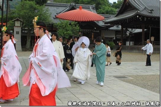 八坂神社-紙園祭,\新人的前面有兩位前導,還有人為新娘特別撐傘,後面還跟著家屬及賓客,其實旁邊還有穿西裝的人員維持秩序,排除擋道的遊客。