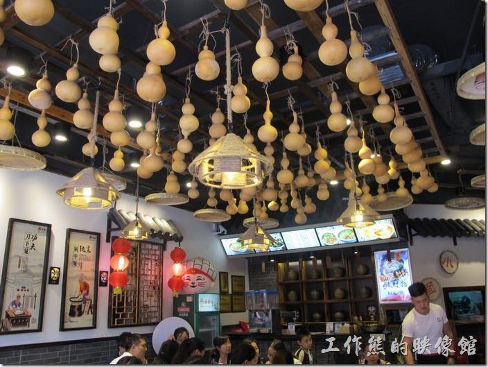 甪竹古鎮旁的貓婆小麵重慶小麵館內的裝潢,花板上吊了很多的葫蘆,燈具上的遮光罩利用農家的斗笠裝飾,還有竹編的米篩。