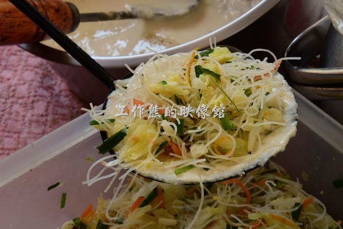 馬祖北竿橋仔村依嬤蚵嗲。然後將米粉絲、蝦皮、高麗菜、紅蘿蔔絲、青蔥等事先拌好的內餡放已經塗抹了一層麵糊的蚵嗲匙上。