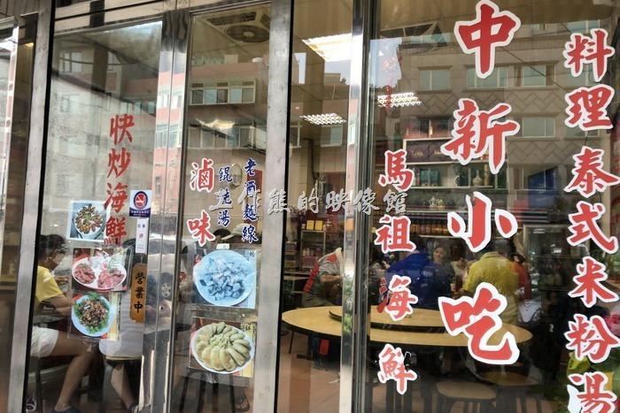 【中新小吃】門口的透明落地窗上貼了各式招牌菜色。