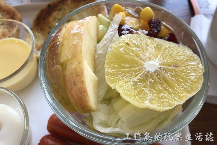 台南-6吋盤早午餐立賢店。沙拉放了一塊切片柳橙,切成小丁的蘋果,放入葡萄乾、葵花子、玉米,底下放了生菜,可以淋上優格醬。