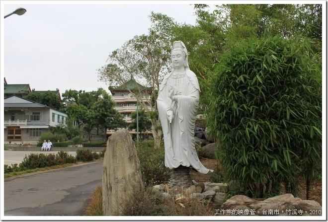 寺前的路口矗立者一尊「觀音菩薩」像,後面隱約可見納骨塔,背景有兩個修行的尼姑。